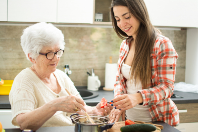 senior woman with granddaughter cooking in the kitchen